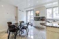 fully equipped modern kitchen with a dining table and 4 seats in a 3-bedroom Paris luxury apartment