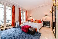 contemporary stylish spacious master bedroom with queen size bed in a 3-bedroom Paris luxury apartme
