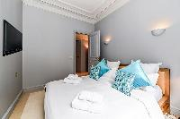 second bedroom with comfortable sleeping amenities and plenty of closets in a 3-bedroom Paris luxury