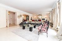 stylish open living area with beautiful dark wooden floors and a big flat screen TV in a 3-bedroom P