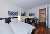 lovely bedroom with 2 single beds, study table, and an en suite bathroom with shower and toilet