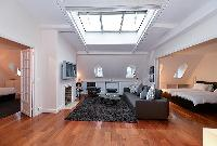 charming living room with large sofa, a flat screen TV, and a glass center table on top of a beautif