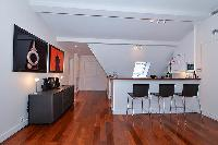 modern well-equipped kitchen and breakfast bar with 3 chairs in paris luxury apartment
