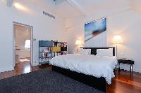 master bedroom with a king size bed, a television, and an en suite bathroom with a tub, shower, and