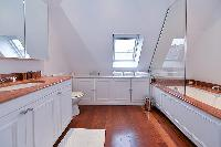 an en suite bathroom with a tub, shower, and a full toilet in paris luxury apartment