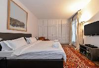 elegant master bedroom with king sized bed, HD TV, leather couch, closet, French wndow and drape cur