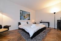 cozy bedroom with king-sized bed, parquet floor, grey carpet rug and armchair in paris luxury apartm