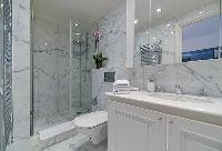 bathroom with marble lavatory, shower, and toilet in paris luxury apartment