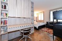 cozy bedroom with a couch, study table, bookshelves, and ample storage in paris luxury apartment