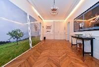 hallway with parquet floor and work of arts hanged on the wall in a 3-bedroom paris luxury apartment