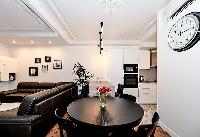 cozy dining area with an elegant and shiny round dining table with chairs in a 2-bedroom Paris luxur