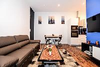 modern and chic living area with a comfortable sofa bed, a huge HD Television, a lovely carpet, and