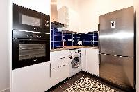 fully-equipped modern kitchen with a large, sleek 2-door fridge, an oven, and a window that opens to