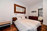 modern master bedroom with a king-sized bed, ample storage space, a safe, and a television in a 1-be