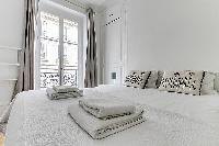 bedroom with a queen size bed and tall glass window fronting the street in paris luxury apartment