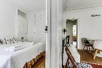 bedroom with a queen size bed with access to the living area in paris luxury apartment
