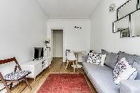 bright and warm living room with grey sofa, stylish lamp, a television and three-seater dining area