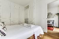 chic master bedroom with access to the living area in paris luxury apartment