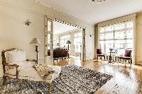 living room with ample seating, numerous lamps, an elegant center table, and elegant carpentry in a