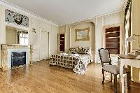 bedroom  with queen-sized bed, varying duvet colors and room wall decals in a 4-bedroom Paris luxury