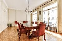 elegant dining room with long, rectangular dining table with 8 seats and tall bright windows, and ch