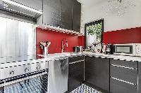 fully-equipped red and grey kitchen in a Paris luxury apartment