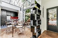 rectangular, glass table and seats for 4 people in a Paris luxury apartment