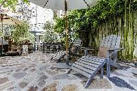relaxing courtyard with table and chairs, and potted plants in a Paris luxury apartment