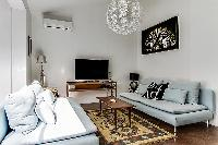 spacious living room with modern décor, cozy sofas, and a lounge seat in a Paris luxury apartment