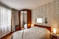 cozy bedroom with a queen-sized bed, lamps, and ample storage in a 1-bedroom Paris luxury apartment