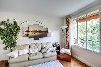 comfortable sofa, potted plants, lamps, and bright windows with the views outside in a 1-bedroom Par