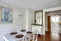 dining room with a mirror, square-shaped table and seats for 4, and kitchen in a 1-bedroom Paris lux