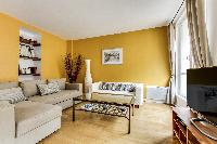 cozy living room with rich yellow walls, two Scandinavian-style double-sized sofa beds, and entertai