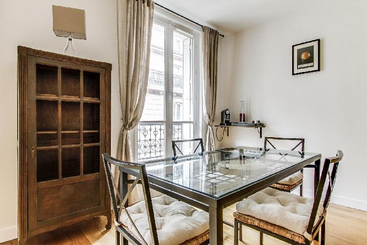 dining area highlighted by a glass table with 4 matching seats in a Paris luxury apartment