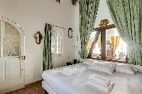a romantic bedroom with two single beds joined together by a queen-size mattress in Paris luxury apa