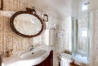 en-suite bathroom with a shower area, a toilet, a sink and a mirror in Paris luxury apartment