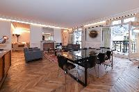 elegant dining table with 8 seats,living area, French windows with balcony, and parquet floor in par