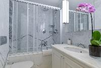 bathroom with marble lavatory, shower, toilet and bathtub in a 5-bedroom paris luxury apartment