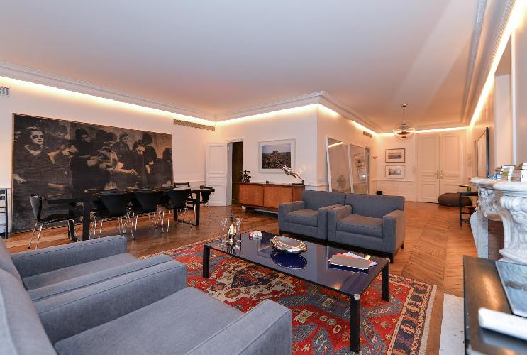 elegant living area with grey sofas, glass center table, and dining area in a 5-bedroom paris luxury