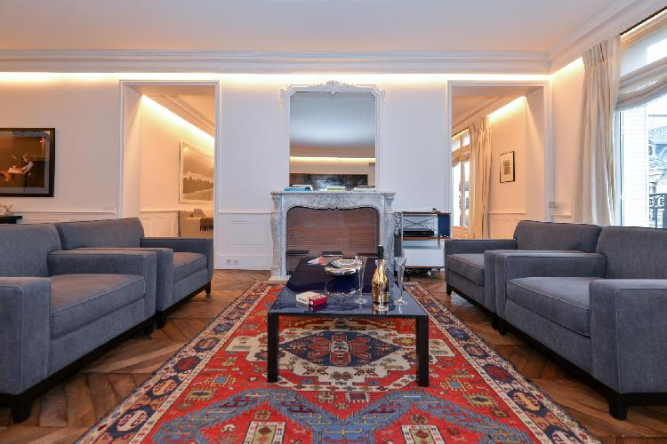 elegant living area with grey sofas, glass center table, ornamental fireplace and mirror in a 5-bedr