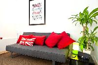 comfy couch with red pillows and Union Jack accent in London Charming and Modern Camden luxury apart