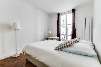 first bedroom with a queen size bed in a 2-bedroom Paris luxury apartment