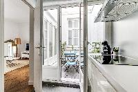modern and fully equipped kitchen and terrace in a 2-bedroom Paris luxury apartment