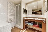spacious well-maintained and neat bathroom with bathtub, shower and sinks in a 4-bedroom Paris luxur