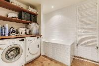 spacious well-maintained and neat bathroom with bathtub and washier and dryer in a 4-bedroom Paris l