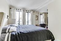 master bedroom with a king-size bed and a full en suite bathroom in a 4-bedroom Paris luxury apartme