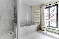 spacious well-maintained and neat bathroom with bathtub and shower in a 4-bedroom Paris luxury apart