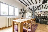 lovely dining area with a sturdy wooden dining table with seats and exposed beams in a 4-bedroom Par