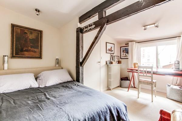 second bedroom with a queen-size bed, studytable and chair, and exposed beams in a 4-bedroom Paris l